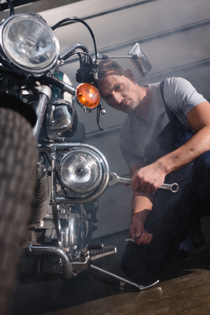 handsome mechanic holding wrench and fixing motorcycle engine in garage