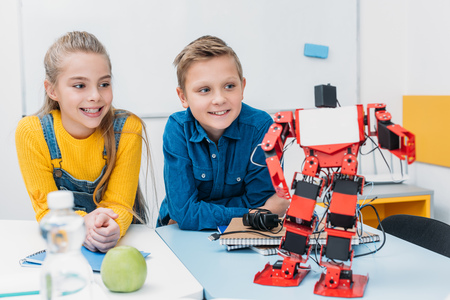 smiling schoolchildren sitting at desk and looking at red plastic robot in stem class 写真素材