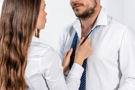 cropped image of girlfriend tying boyfriend tie in morning at home, social role concept