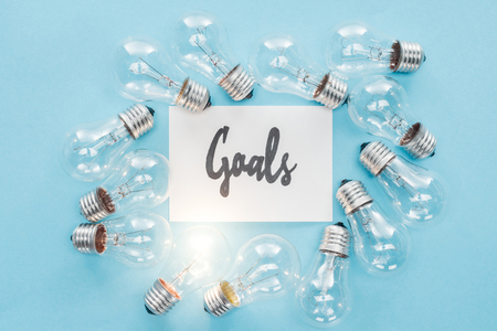 top view of goals word written in cursive on card surrounded by circle of light bulbs on blue background, goal setting concept