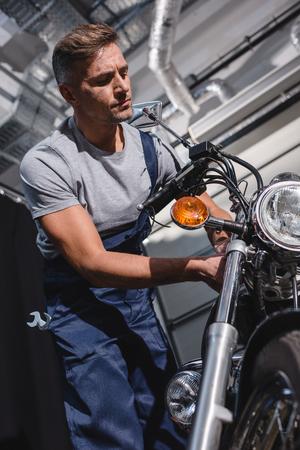 handsome adult mechanic in overalls fixing motorcycle in garage