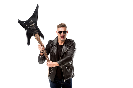 excited adult man in leather jacket holding electric guitar isolated on white