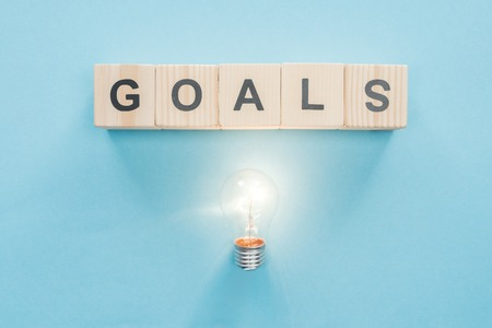 top view of glowing light bulb under goals word made of wooden blocks on blue background, goal setting concept