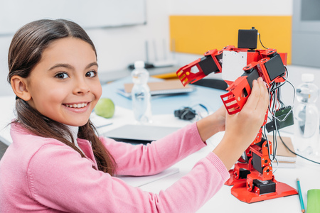 adorable schoolgirl sitting at table, holding robot model at STEM classroom and looking at camera