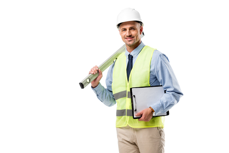 smiling engineer holding clipboard and spirit level isolated on white