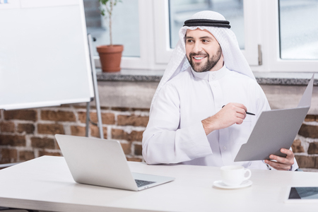 Arabian businessman holding folder and pen in office
