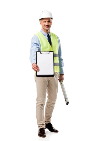 smiling engineer holding clipboard with blank sheet and spirit level isolated on white Stock Photo