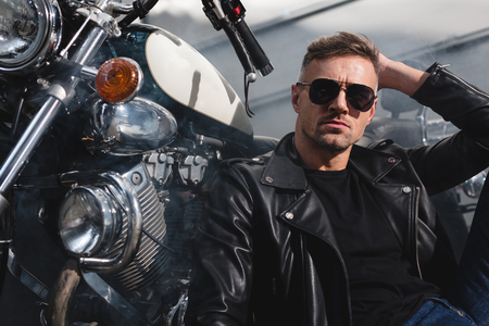 handsome guy in sunglasses sitting by motorcycle in garage