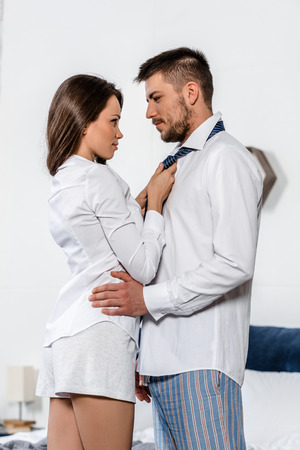 low angle view of girlfriend tying boyfriend tie in morning on weekday in bedroom, social role concept Stock Photo
