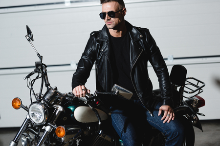 handsome classic man in black sunglasses and leather jacket standing by motorcycle in garage Stock Photo