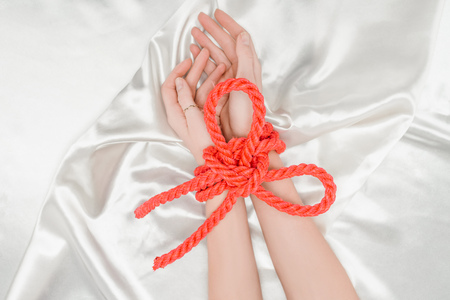 cropped view of female hands bounded with bright red rope