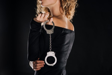 partial view of curly woman holding silver handcuffs isolated on black