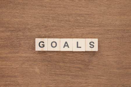 top view of 'goals' word made of wooden blocks on wooden tabletop, goal setting concept