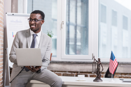 African american businessman holding laptop in modern office Stock Photo