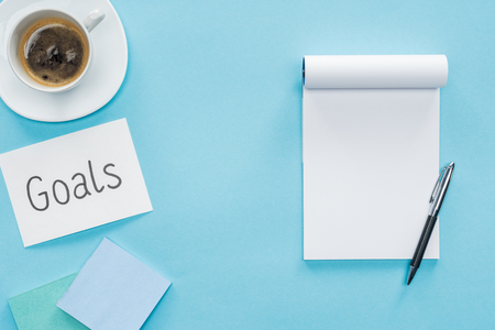 top view of card with goals lettering, blank notebook and cup of coffee on blue background, goal setting concept Stock Photo