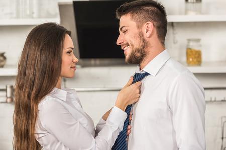 portrait of girlfriend tying smiling boyfriend tie in morning at kitchen, sexism concept