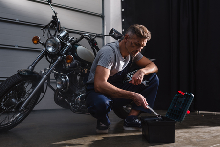 mechanic putting tools away after fixing motorbike in garage