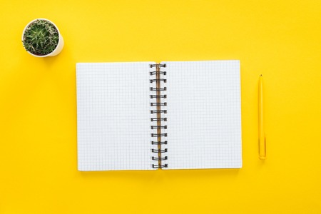 top view of blank spiral notebook and pen on yellow background Foto de archivo