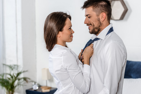 side view of cheerful girlfriend tying boyfriend tie in morning on weekday in bedroom, social role concept