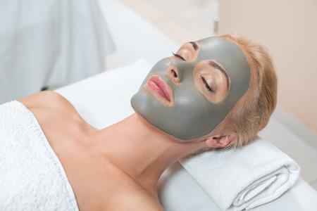Nahaufnahme einer blonden Frau, die mit Gesichtsmaske aus Ton im Spa liegt?