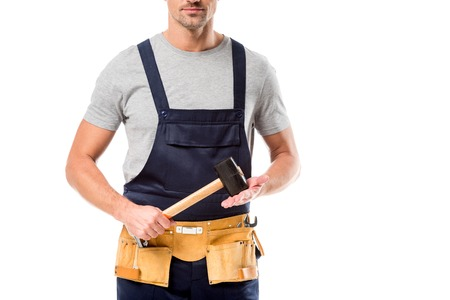 partial view of worker in overalls holding hammer isolated on white