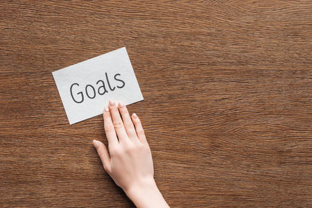 partial view of woman pointing at 'goals' lettering on card with wooden background