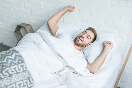 high angle view young man yawning and stretching in bed 版權商用圖片