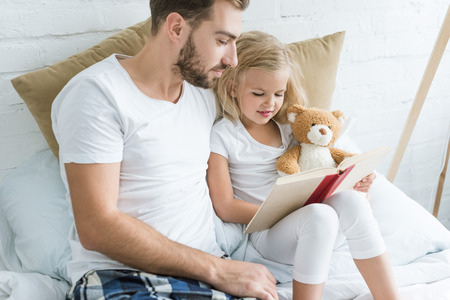 father and adorable little daughter reading book together on bed