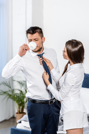 girlfriend tying boyfriend tie while he drinking coffee in morning at home, social role concept