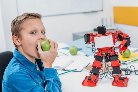 cheerful boy eating apple after STEM robotics lesson 免版税图像