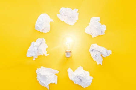 glowing light bulb in circle of crumbled paper balls on yellow background, having new ideas concept