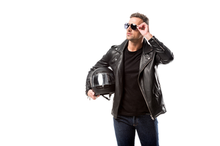 man in leather jacket and sunglasses holding motorcycle helmet and posing isolated on white