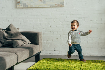 happy little boy running in living room at home Stock Photo - 112989671