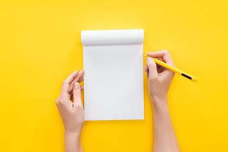Vista parcial persona sujetando la pluma sobre un cuaderno en blanco sobre fondo amarillo Foto de archivo