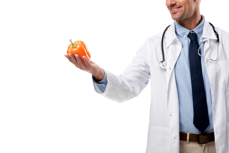 cropped view of doctor holding bell pepper isolated on white, healthy eating concept