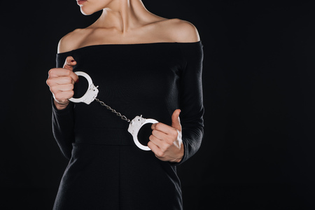 partial view of woman holding handcuffs isolated on black Stock Photo - 112989893
