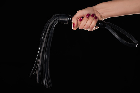 cropped view of female hand holding leather flogging whip isolated on black