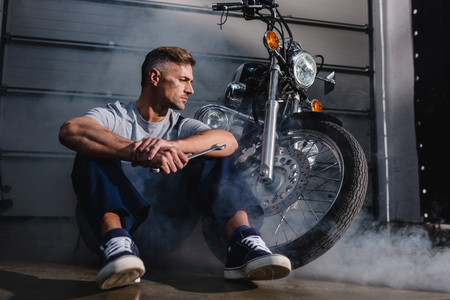handsome mechanic looking away, holding wrench and sitting near motorcycle in garage