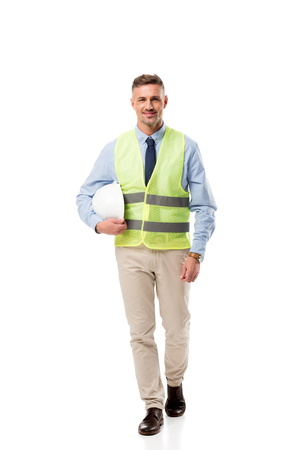 smiling engineer in safety vest holding helmet and looking at camera isolated on white