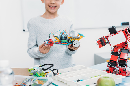cropped view of schoolboy presenting handmade robot model at STEM lesson