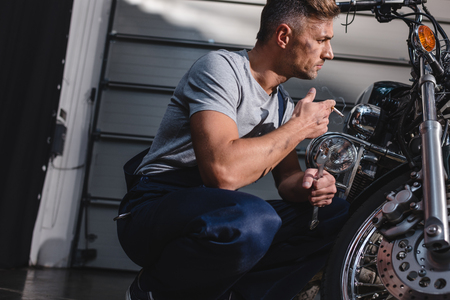 mechanic checking motorcycle front wheel and smoking in garage Banque d'images - 112989958