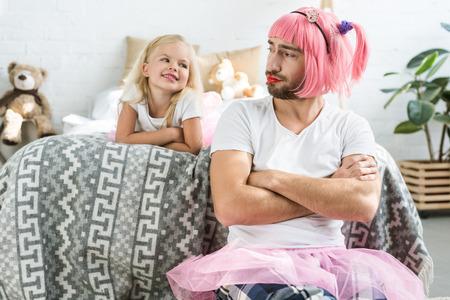 entzückende glückliche Tochter, die Vater in rosa Perücke und Tuturock anschaut Standard-Bild
