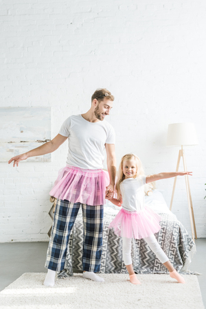 happy father and cute little daughter in pink tutu skirts holding hands and dancing at home
