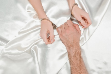 cropped view of male hand holding handcuffs on woman hands