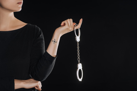 partial view of woman holding metal handcuffs isolated on black