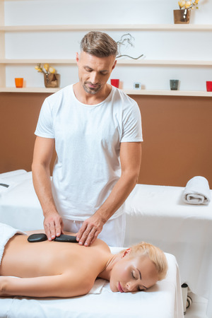 Handsome therapist putting hot stones on back of woman Stock Photo - 112990020
