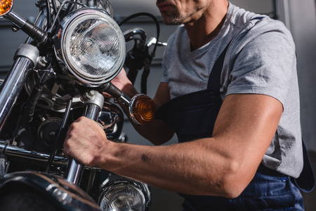 cropped view of mechanic fixing motorcycle headlamps in garage