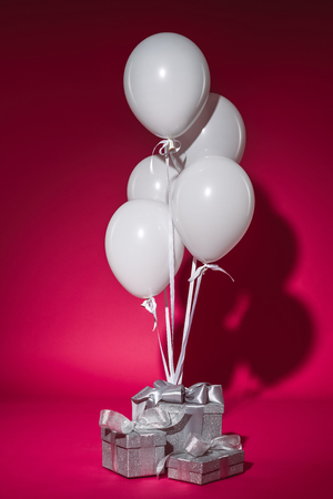 bundle of white balloons and silver gift boxes on burgundy