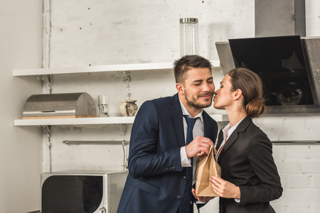 girlfriend giving lunch to boyfriend and kissing him in morning at kitchen, social roles concept Stock Photo