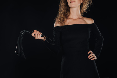 partial view of woman holding leather flogging whip in hand isolated on black
